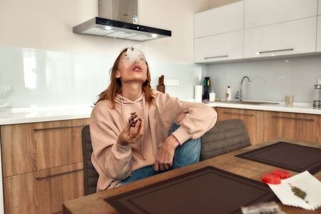Young caucasian woman exhaling the smoke while smoking marijuana from a glass pipe, sitting in the kitchen. Red weed grinder on the table. Cannabis legalization concept. Selective focus
