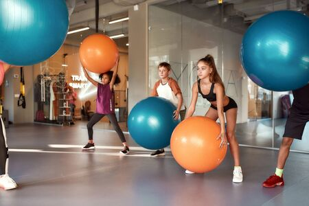 Full length shot of kids working out using exercise ball in gym. Sport, healthy lifestyle, physical education concept