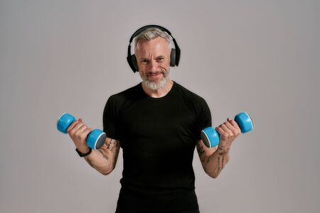 Train more. Middle aged muscular man in black t shirt and headphones smiling at camera holding blue dumbbells, posing in studio over grey background Standard-Bild