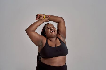 Love my body. Plump, plus size african american woman in sportswear laughing, lifting her arms up in studio over grey background. Concept of sport, healthy lifestyle, body positive, equality Standard-Bild