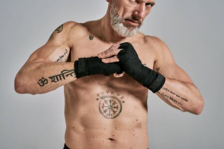 Half naked middle aged athletic man, kickboxer warming up wrapped hands before training standing in studio over grey background