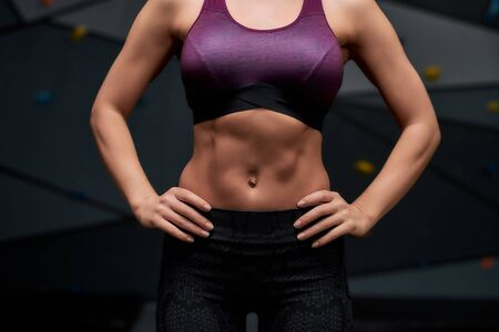 Cropped shot of active young woman in sportswear showing her sportive body, abs, standing against artificial training climbing wall. Concept of sport life and rock climbing Standard-Bild