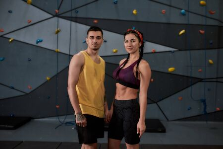 Active young man and woman in sportswear looking at camera, standing against climbing wall. Concept of sport life and rock climbing Standard-Bild