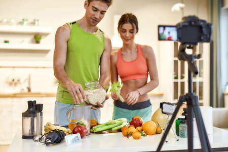 World of possibilities. Young couple recording video blog or vlog about healthy nutrition on camera at home. Man and woman showing ingredients and explaining how to prepare, standing in the kitchen