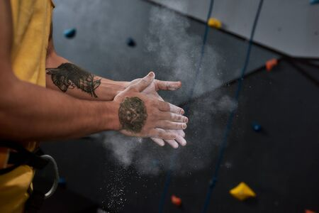 Cropped shot of sportive man applying white dust of magnesia, chalk on hands before climbing wall in bouldering center. Concept of sport life and rock climbing