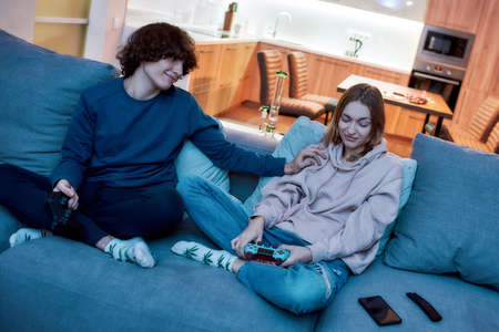 Dont worry. Young couple playing video games after smoking marijuana from a bong while sitting on the couch at home Stock fotó