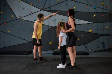 Active little girl going to climb, male and female instructor helping kid, standing against artificial training climbing wall. Concept of sport life and rock climbing. Selective focus on people