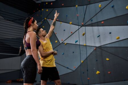 Adjust Your Altitude. Active young woman in sportswear going to climb, male instructor helping her, standing against artificial training climbing wall. Concept of sport life and rock climbing Standard-Bild