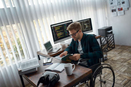 Developing myself. Young male web developer in a wheelchair reading a book while sitting at his workplace with multiple computer screens on the background Reklamní fotografie