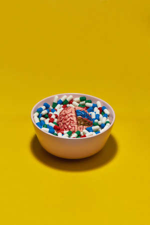 Creative concept with different medical pills, capsules lying in bowl with model of human brain on yellow background. Health care and treatment concept