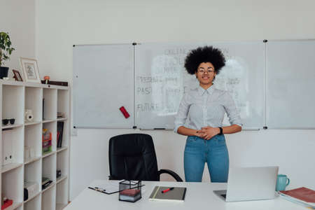 English teacher. Portrait of young cheerful afro american woman in casual clothes looking at camera and smiling while teaching English language online from home Reklamní fotografie