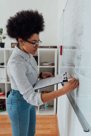 Teaching English language from home. Close up shot of a young afro american female teacher in glasses holding folder with document and writing something on a whiteboard