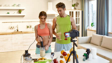 Influencing Future with Videos. Young couple recording video blog or vlog about healthy nutrition on camera at home. Man and woman showing how to prepare smoothie, standing in the kitchen