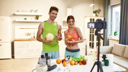 Capturing ideas. Young couple recording video blog or vlog about healthy nutrition on camera at home. Man and woman showing ingredients and explaining how to prepare a meal, standing in the kitchen Stok Fotoğraf