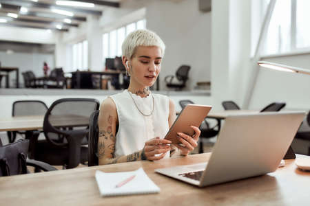 Talking online. Young blonde tattooed business woman in wireless earphones using her touchpad, having skype call with client while sitting at her working place in the office