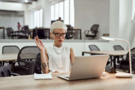 Difficult task. Young blonde tattooed business woman with short haircut wearing wireless earphones, holding pen in her hand and working with laptop while sitting at her working place in the office Stok Fotoğraf