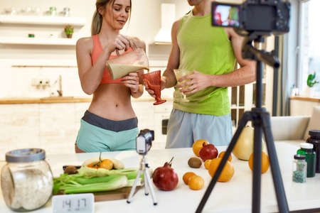 Bringing your creativity to life. Cropped shot of couple recording video blog or vlog about healthy nutrition on camera at home. Man and woman showing how to prepare smoothie, standing in the kitchen Stok Fotoğraf