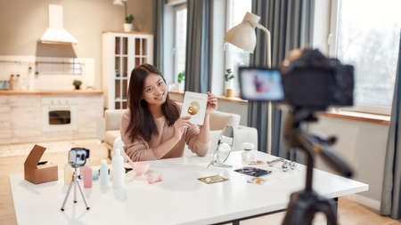 The audience is my priority. Young female blogger recording a tutorial video for her beauty blog about skincare routine. Vlogger showing face mask and broadcast live video to social network