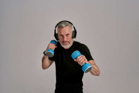 Middle aged muscular man in black t shirt and headphones looking at camera holding blue dumbbells, posing in studio over grey background