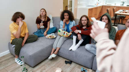 Young multicultural people eating snacks, playing video games after smoking marijuana from a bong while sitting on the couch. Side view