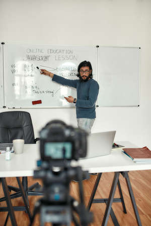 Live stream. Young bearded male teacher wearing glasses pointing at whiteboard and giving Javascript lesson online, recording video blog Stok Fotoğraf