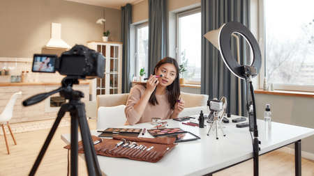 Feel the social experience. Asian female blogger applying makeup while recording a tutorial video for her beauty blog using camera at home Stok Fotoğraf