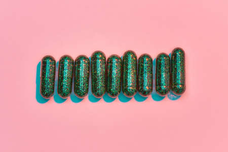Creative concept with many green glitter pills lying in a row horizontally isolated on pastel pink background. Minimal style, art concept