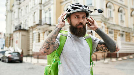 Helping you. Brutal bearded delivery man wearing helmet while standing with thermo bag or backpack outdoors, ready to ride a bicycle. Courier, delivery service concept