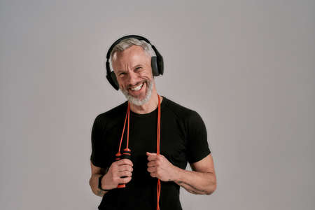 Middle aged muscular man in black t shirt and headphones smiling at camera holding jump rope, posing in studio over grey background 版權商用圖片