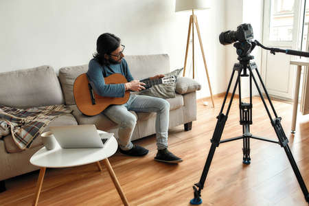 Giving guitar online lesson. Young man blogger or music teacher sitting on sofa with a guitar, recording video tutorial at home