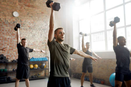 Active Lifestyle. Young athletic man lifting dumbbell while having workout at industrial gym. Group training concept