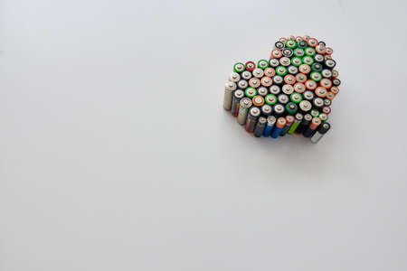 Many alkaline batteries in the shape of a heart on white background. Concept of recycling waste and environmental pollution