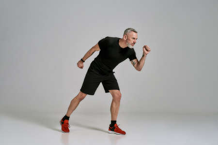 Full length shot of middle aged muscular man in black sportswear looking aside while exercising in studio over grey background 版權商用圖片