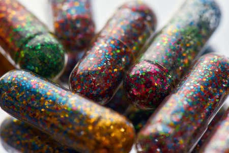 Creative concept with many colorful glitter pills scattered, lying randomly. Minimal style, art concept