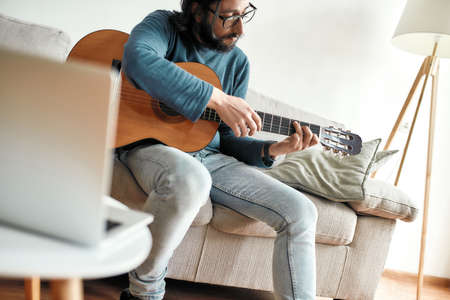 Guitar player. Young man playing guitar while sittting at home and watching video tutorial on laptop online. Distance education 免版税图像
