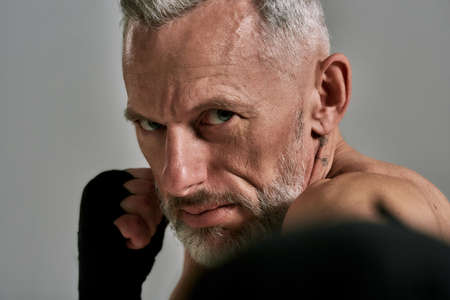 Close up of middle aged athletic man, kickboxer looking agressive while boxing, training in studio over grey background. Muay Thai, Boxing or Kickboxing concept