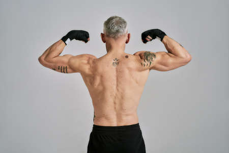 Half naked middle aged athletic man, kickboxer showing his body, while exercising, practicing punches in studio over grey background