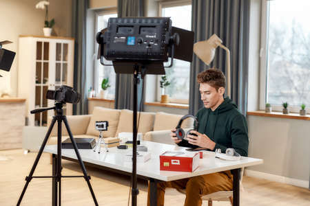 Sharing opinion. Young male technology blogger recording video blog or vlog about new headphones and other gadgets at home studio. Blogging, Work from Home concept Stockfoto