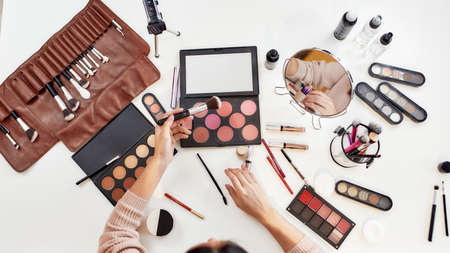 Top view of young woman, artist doing makeup, sitting at the table. Closeup female hands applying make up. Cosmetic advertising concept. Focus on hands. Web Banner