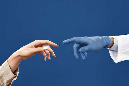 Connection between doctor and patient. Hands of doctor in sterile glove and female patient touching each other with fingers. Isolated on navy blue background. Cropped shot. Medical care, healthcare