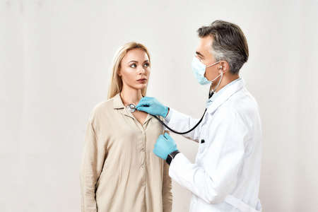Medical care. Professional male doctor in medical uniform and protective mask using stethoscope, checking lungs and heart of a young woman, female patient Imagens