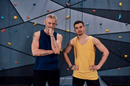 Young male instructor and middle aged man looking at camera, while standing against climbing wall. Concept of sport life 版權商用圖片