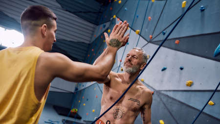 Muscular middle aged man in safety equipment and harness giving high five young male instructor after training on the artificial climbing wall