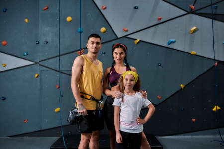 Young male instructor with woman and girl looking at camera, standing against artificial training climbing wall