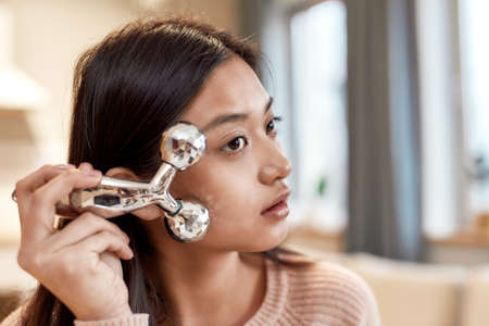 Get the face you want. Close up of young female blogger massaging her face with facial roller while recording a video for her beauty blog. Face lift, anti aging treatment concept