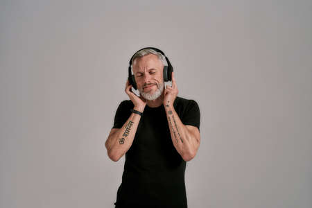 Middle aged muscular man in black t shirt and headphones closing his eyes while listening to music in studio over grey background Archivio Fotografico