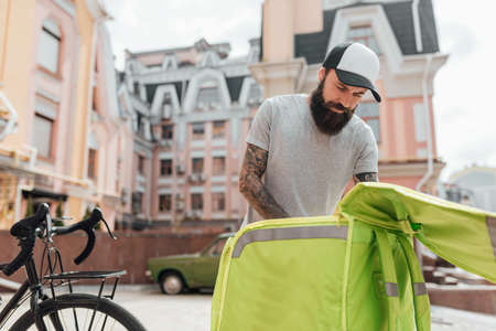 Meal delivery. Brutal stylish delivery man taking food out of thermo bag standing outdoors with bike. Courier, delivery service concept 스톡 콘텐츠