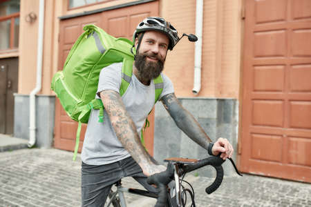 Perfect Delivery. Bearded delivery man in helmet with thermo bag or backpack smiling at camera, riding a bike along the city, delivering food. Courier, delivery service concept