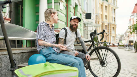 Two cheerful couriers, young man and woman sitting on the bench and talking outdoors while delivering food and products, using scooter and bike