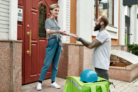 Bearded delivery man with thermo backpack giving away pizza to a female customer, while delivering food. Courier, delivery service concept